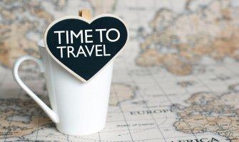 Imagen de un mapa del mundo con una taza y un cartel que dice en ingles: tiempo de viajar