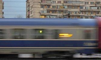 Imagen de un tren de Bucarest en pleno movimiento. Al fondo los edificios